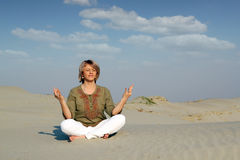 Beautiful woman meditating in desert Royalty Free Stock Photos