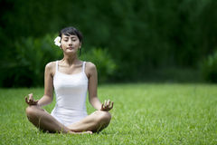 Beautiful Woman meditating in the garden Stock Photos