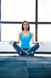 Beautiful woman meditating at gym Royalty Free Stock Photography