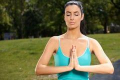 Beautiful woman meditating in park stock photography