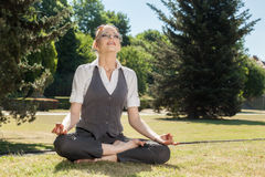 Beautiful woman meditating in the park Stock Photo