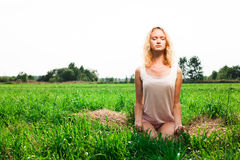 Beautiful woman meditating in summer park Stock Photo