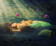 Beautiful woman mermaid. With a fish tail resting in the water of the pond of lilies Royalty Free Stock Photo