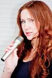 Beautiful woman with a microphone in hands Stock Images