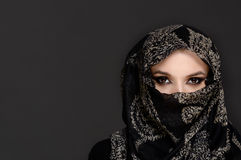 Beautiful Woman in Middle Eastern Niqab veil. On grey background Stock Image