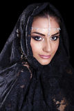 Beautiful Woman in Middle Eastern Niqab veil on isolated black b. Portrait of a beautiful woman with arabian makeup in black paranja isolated on dark background Stock Photo