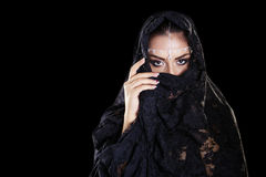 Beautiful Woman in Middle Eastern Niqab veil on isolated black b. Portrait of a beautiful woman with arabian makeup in black paranja isolated on dark background Stock Images