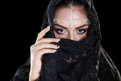Beautiful Woman in Middle Eastern Niqab veil on isolated black b. Portrait of a beautiful woman with arabian makeup in black paranja isolated on dark background Stock Photos