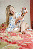 Beautiful woman with a mirror in the bedroom Royalty Free Stock Photos