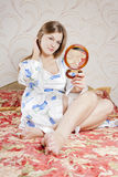 Beautiful woman with a mirror in the bedroom Stock Images