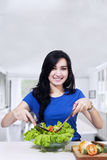 Beautiful woman mixing fresh salad Royalty Free Stock Photography