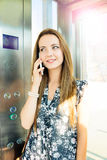 Beautiful woman at mobile phone in an elevator Royalty Free Stock Photography