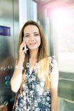 Beautiful woman at mobile phone in an elevator Stock Photos