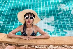Beautiful woman model in bikini and sunglasses fashion relaxing. In resort, summer swimming pool water on holidays stock photography