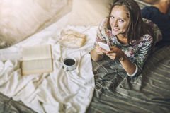 Beautiful woman model with coffee, pastries, home phone on the b. Lanket. Breakfast, morning, home, comfort Stock Photography