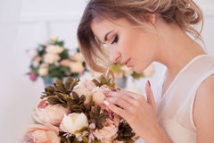 Beautiful woman model with fresh daily makeup and romantic wavy hairstyle, holding a bouquet of flowers. Glamour portrait of beautiful woman model with fresh stock photography