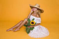 Beautiful woman with long blond hair, wearing a white dress and hat, holding sunflowers. Beautiful woman model girl with long blond hair, wearing a white dress Royalty Free Stock Images