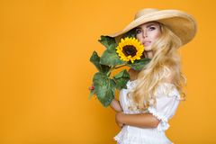 Beautiful woman with long blond hair, wearing a white dress and hat, holding sunflowers. Beautiful woman model girl with long blond hair, wearing a white dress Stock Images