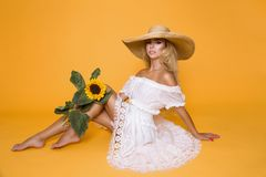 Beautiful woman with long blond hair, wearing a white dress and hat, holding sunflowers. Beautiful woman model girl with long blond hair, wearing a white dress Stock Photo