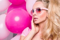Beautiful woman model with long blond hair dressed in a pink dress and sunglasses standing on a red and  pink balloons. Beautiful woman model with long blond Royalty Free Stock Photos