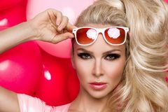 Beautiful woman model with long blond hair dressed in a pink dress and sunglasses standing on a red and  pink balloons Royalty Free Stock Image