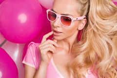 Beautiful woman model with long blond hair dressed in a pink dress and sunglasses standing on a red and  pink balloons Royalty Free Stock Photo