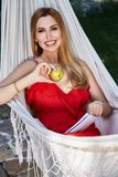 Beautiful woman model with long blond hair lies in a hammock rel Stock Photography