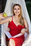 Beautiful woman model with long blond hair lies in a hammock rel Royalty Free Stock Photo