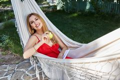 Beautiful woman model with long blond hair lies in a hammock rel Stock Photo