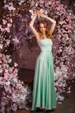 Beautiful woman model in a mint-colored dress on a flowered spring background. Beauty girl with a stunning makeup and hairstyle royalty free stock photo