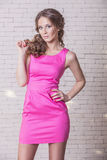 Beautiful woman model in pink short dress against a white  wall. Beautiful woman model in pink short dress against a white brick wall Stock Image