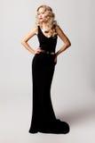 Beautiful woman model posing in elegant dress. Beautiful woman model posing in elegant black dress in the studio royalty free stock image