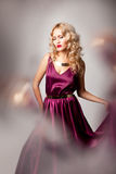 Beautiful woman model posing in elegant dress. Beautiful woman model posing in elegant purple silk dress with frame of reflection in the studio stock images