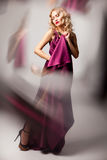 Beautiful woman model posing in elegant dress. Beautiful woman model posing in elegant purple silk dress with frame of reflection in the studio royalty free stock photo