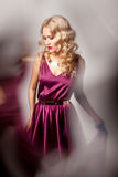 Beautiful woman model posing in elegant dress. Beautiful woman model posing in elegant purple silk dress with frame of reflection in the studio royalty free stock image