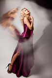 Beautiful woman model posing in elegant dress. Beautiful woman model posing in elegant purple silk dress with frame of reflection in the studio stock photos