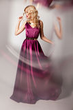 Beautiful woman model posing in elegant dress. Beautiful woman model posing in elegant purple silk dress with frame of reflection in the studio royalty free stock photography