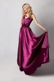 Beautiful woman model posing in elegant dress. Beautiful woman model posing in elegant purple silk dress in the studio royalty free stock images