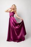 Beautiful woman model posing in elegant dress. Beautiful woman model posing in elegant purple silk dress in the studio royalty free stock photos