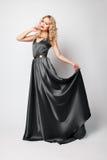 Beautiful woman model posing in gray dress. Beautiful woman model posing in elegant gray silk dress in the studio royalty free stock photo