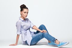 Beautiful woman model posing in jeans and shirt and sneakers in the studio. Caucasian, elegance. Full portrait of the beautiful young woman with  black hair Royalty Free Stock Image