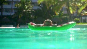 Beautiful woman model size plus in sunglasses relaxing on the mattress on the water. Concept vacation, tourism