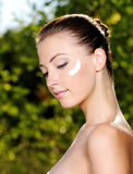 Beautiful woman with moisturizer cream on cheek Royalty Free Stock Photography