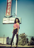 Beautiful woman motel sign. Beautiful exotic young woman posing fashion glamor style beside route 66 motel sign in USA Royalty Free Stock Photos