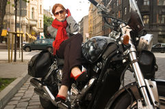 Beautiful woman on the motorcycle. In red scarf royalty free stock images
