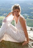 Beautiful Woman on Mountaintop. A portrait of a pretty young woman in a white dress, sitting on top of a mountain with a gorgeous view behind her Stock Photos