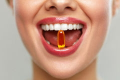 Beautiful Woman Mouth With Pill In Teeth. Girl Taking Vitamins
