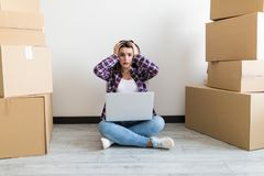 Beautiful woman moving in her new house and unpacking, she is sitting on the floor surrounded by boxes, using a laptop looking sho royalty free stock photography