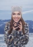 Beautiful woman with mug in ski resort, winter season Stock Photography