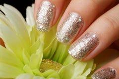 Beautiful woman nails manicure. Touching green flower Stock Photo